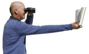 Nearsighted man using binoculars to read